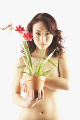 Nude Asian woman holding potted