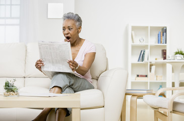 Senior African American woman reading newspaper
