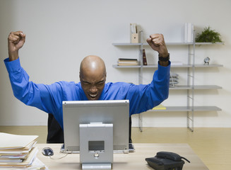African American businessman cheering at desk