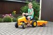 Kind im Sommer fährt Traktor