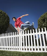Hispanic man jumping over fence