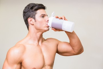 Close-up of a sporty young man drinking protein