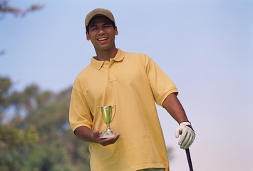Hispanic man holding golf trophy