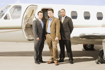 Multi-ethnic businessmen in front of airplane