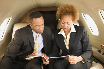 African American businesspeople on airplane
