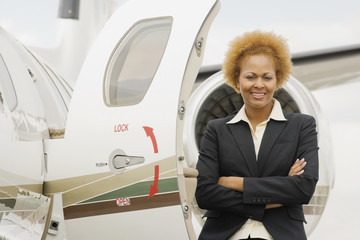 African American businesswoman next to airplane