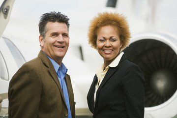 Multi-ethnic businesspeople next to airplane