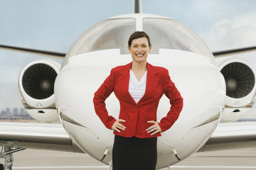 Businesswoman in front of airplane
