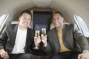 Multi-ethnic businessmen toasting on airplane
