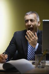 Middle Eastern businessman yawning at desk