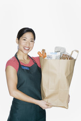Asian woman wearing apron and holding grocery bag