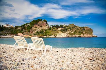 chaise longues on a pebble beach