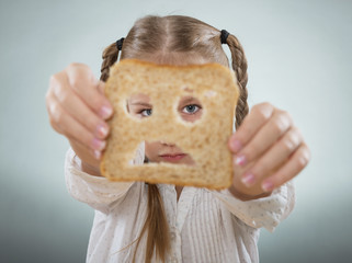Little girl holding her face in front of a sad slice of bread