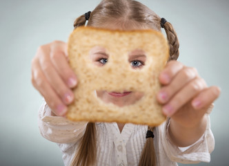 Little girl holding in front of his face, a happy slice of bread