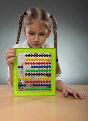 Beautiful little girl use abacus board