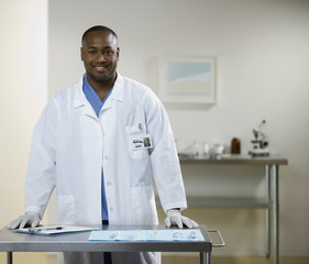 African American male doctor leaning on cart