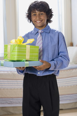 Mixed Race boy holding gifts