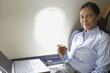 Hispanic businesswoman on airplane