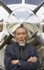 Asian businessman in front of airplane