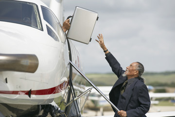 Asian businessman reaching for briefcase
