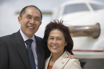 Asian couple next to airplane