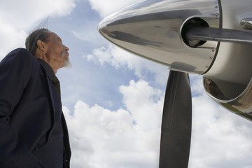 Asian businessman looking at airplane