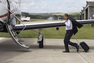 Asian businessman walking towards airplane