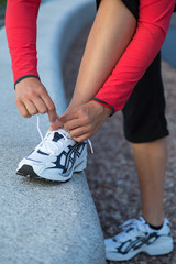 Female hands tying running shoes laces