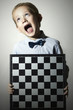 Little boy with chessboard.Chess.Emotion.Scream child
