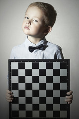 Little boy with chessboard.Chess.Emotion.Serious child