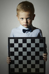 Little boy with chessboard.genius Child.Serious. Chess game