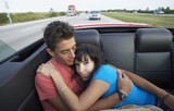Multi-ethnic couple in back of convertible