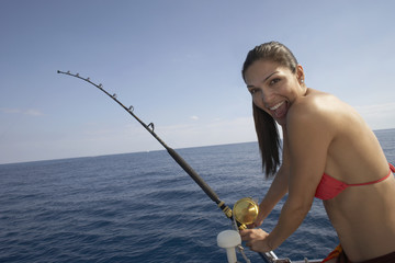 Hispanic woman fishing on boat