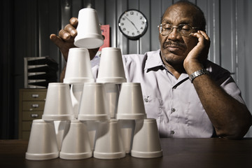 Senior African American male worker stacking cups