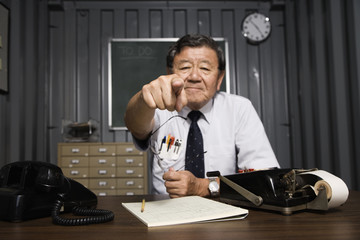 Senior Asian businessman pointing behind desk