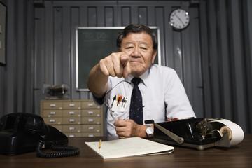 Senior Asian businessman pointing behind desk