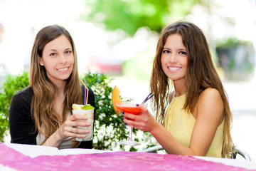 Two friends having a cocktail outdoor