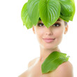 beautiful yoiung cheerful woman with green leaves near her face,