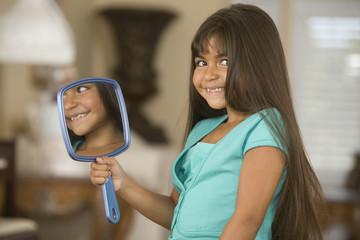 Hispanic girl holding mirror