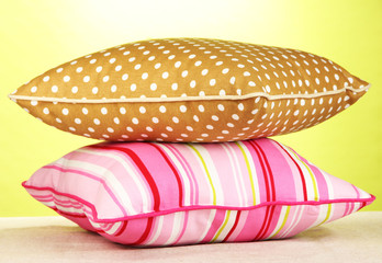 Pink and brown bright pillows on green background