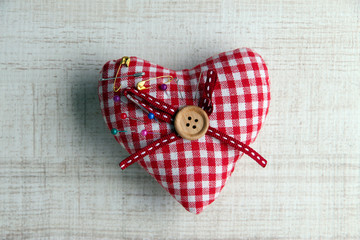 Fabric heart with color  pins on wooden background