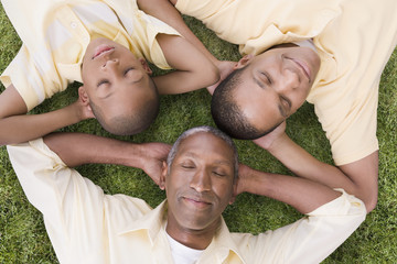"""African American grandfather, father and son laying in grass"""