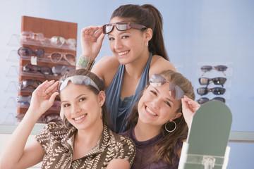 Multi-ethnic teenaged girls trying on sunglasses