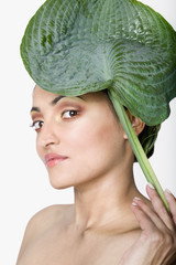 Indian woman holding leaf in front of head