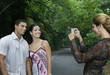 Hispanic woman taking photograph of couple