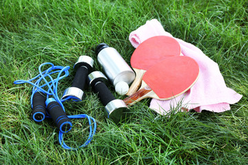 Assortment of sport equipment on green grass background
