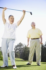 Senior Asian woman cheering on golf course