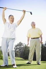 Senior Asian woman cheering on golf course