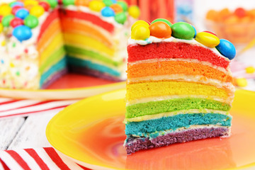 Delicious rainbow cake on plate on table close-up