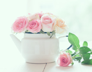 roses in a white enameled vintage teapot